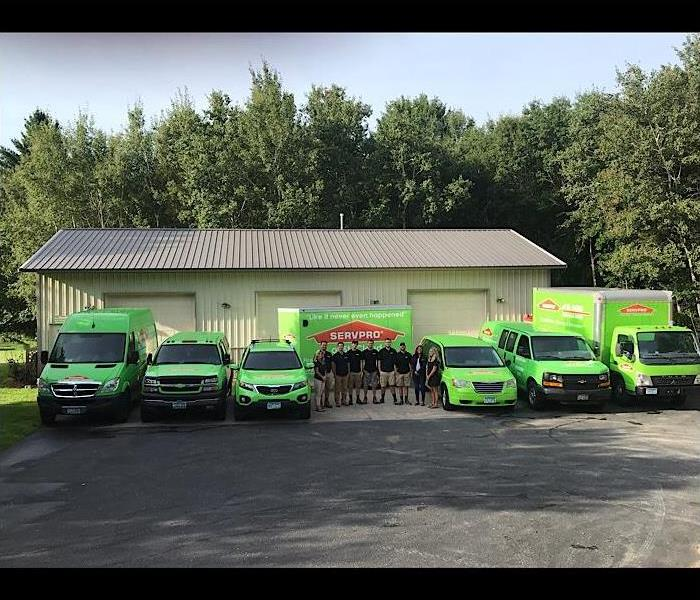 Group photo of the team at SERVPRO of St. Cloud standing in front of all the green vehicles.