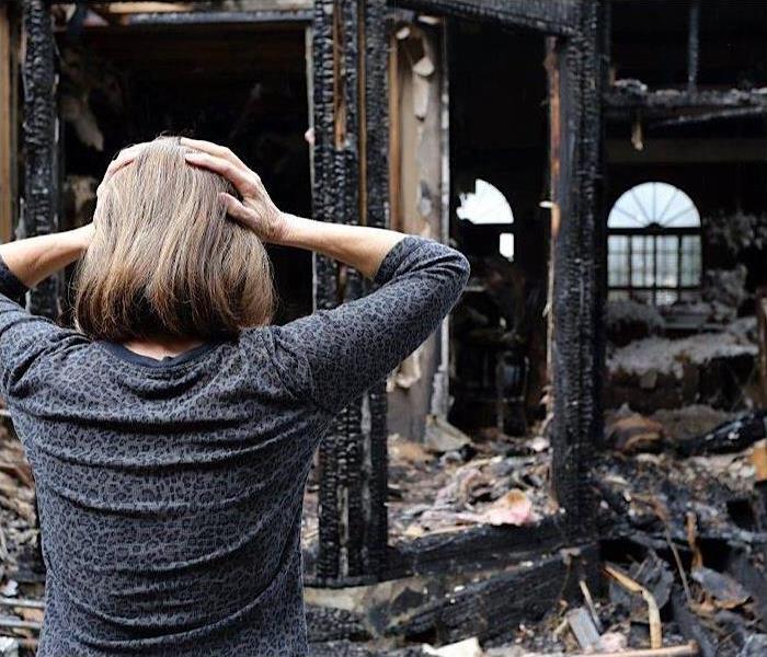 A lady with her hands on her head looking at her house that experienced fire damage.