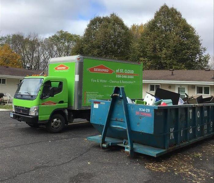 SERVPRO of St. Cloud van by a dumpster with items that were not savable from water damage.